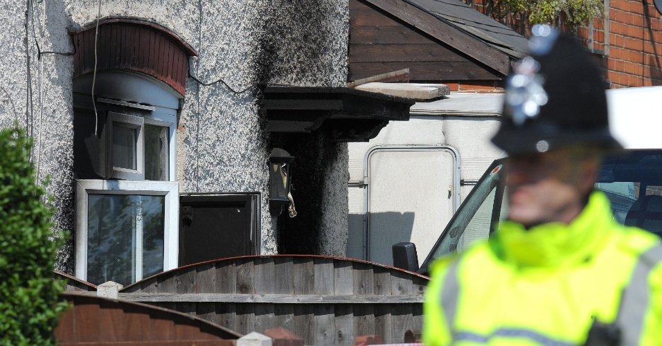 11.mai.2012 - Policial passa em frente a casa, nesta sexta-feira (11), onde cinco crianças morreram após incêndio em Derby, no centro da Inglaterra (Reino Unido). A polícia britânica prendeu uma mulher suspeita de ser responsável pelo incêndio