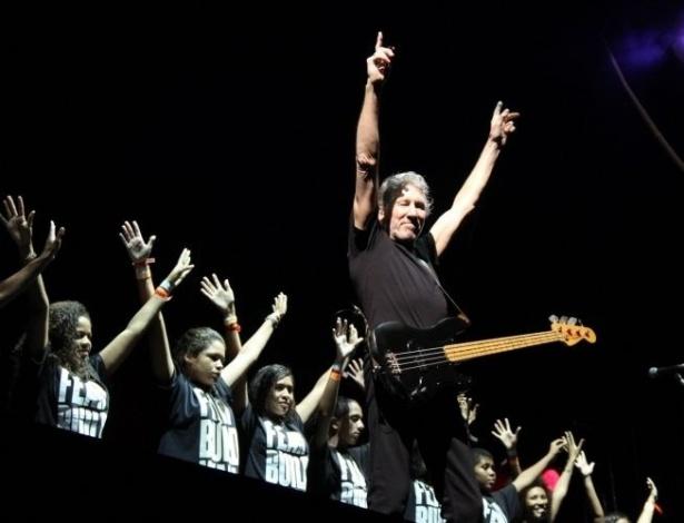 """""""Another Brick in the Wall"""", do Pink Floyd, é uma das músicas mais lembradas quando o assunto é a crítica ao sistema educacional. Logo no começo, a letra já afirma: """"Não precisamos de nenhuma educação. Não precisamos de controle mental"""". Na foto, Roger Waters, ex-integrante do Pink Floyd, canta com jovens da escola de música da Rocinha, em apresentação da turnê """"The Wall"""" no Engenhão, Rio de Janeiro, em março deste ano"""