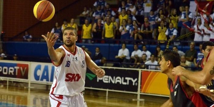 Olivinha, ala-pivô do Pinheiros, recebe a bola marcado de perto por jogador do Joinville durante partida em São Paulo