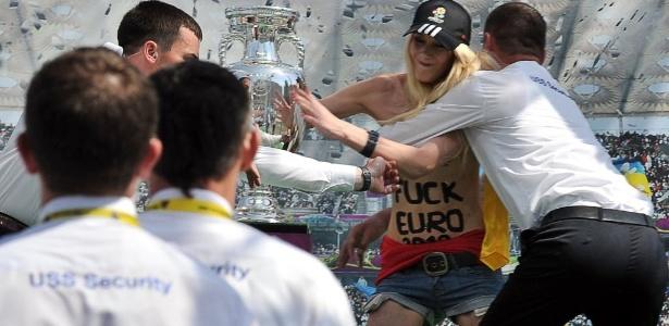 Segurança detém ativista do grupo ucraniano Femen, que atua pelos direitos das mulheres, quando ela tentava se aproximar da taça da Eurocopa 2012, em evento em Kiev, no último dia 12. O grupo protestou contra a expectativa de aumento da prostituição durante o campeonato