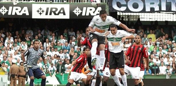 Jogadores do Coritiba sobem após bola cruzada na área para tentar cabeceio na partida contra o Atlético-PR