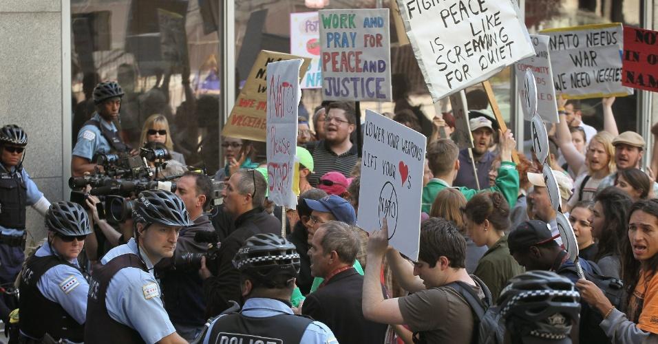 14.mai.2012 - Polícias tentam conter trabalhadores católicos durante protesto realizado fora do edifício Prudential, que abriga a sede da campanha nacional do presidente Barack Obama, em Chicago (EUA). Oito pessoas foram  presas ao tentarem invadir o prédio. Os manifestantes exigem o fim da guerra