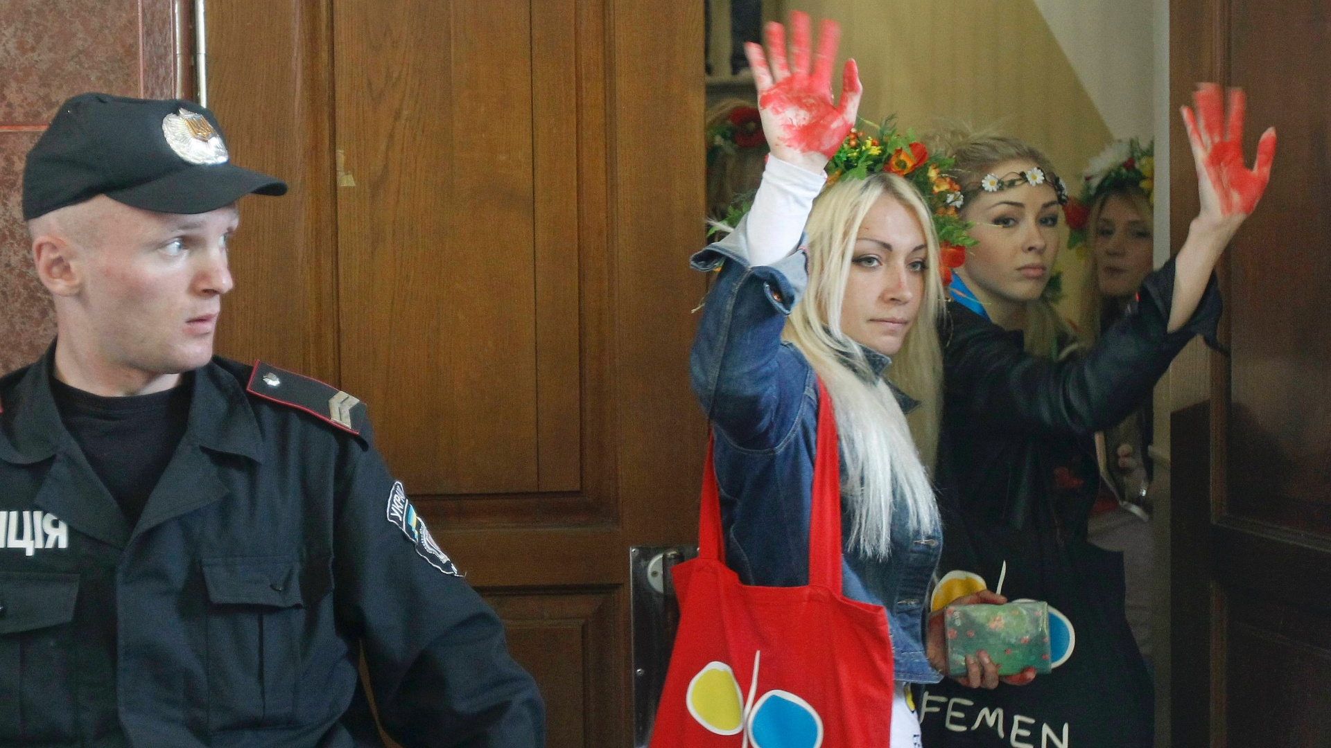 15.mai.2012 - Ativistas do grupo feminista ucraniano Femen acenam para seus apoiadores ao chegar nesta tera-feira (15)  corte de Kiev, na Ucrnia. Elas sero julgadas por dois crimes, um deles sobre fazer topless em pblico - marca do movimento
