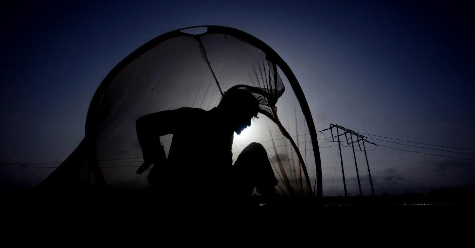 15.mai.2012 - Homem se protege de mosquitos enquanto descansa em cima de caminhão que carrega combustível para os veículos da Otan no Afeganistão, em Karachi, no Paquistão