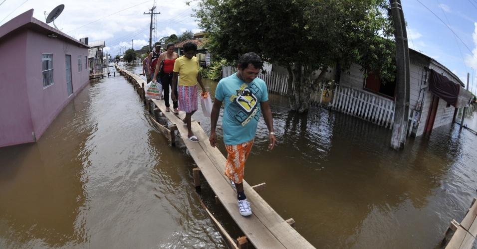 15.mai.2012 - Moradores recorrem à passarela improvisada para passar pelas ruas do município do Careiro da Várzea (AM), castigado pelas cheias dos principais rios do Estado