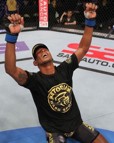 Brasileiro Johnny Eduardo se ajoelha e comemora sua vitória no UFC, diante de Jeff Curran