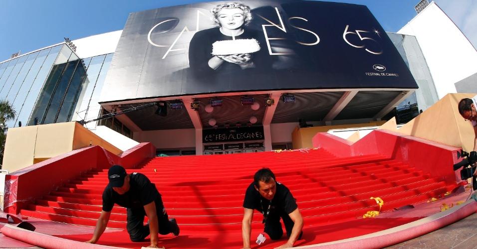 Funcionários instalam o tapete vermelho em frente à entrada principal para abertura do Festival de Cannes 2012 (16/5/12)