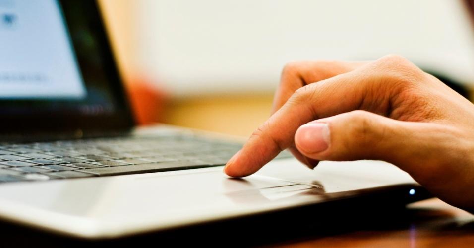 Homem utiliza trackpad de notebook para navegar na internet