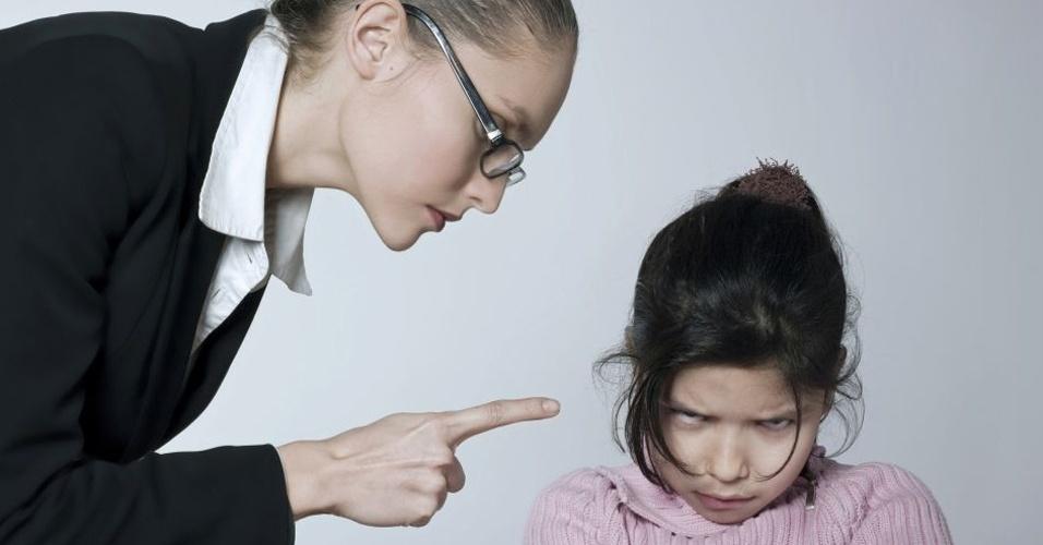 Mulher repreende criança apontando dedo