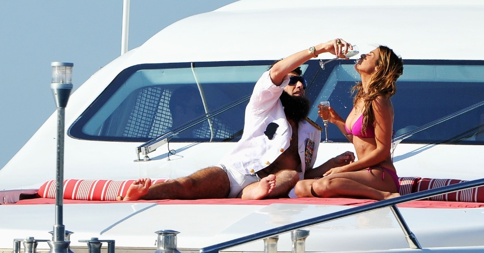 O ator Sacha Baron Cohen, vestido como o General Aladeen, dá bebida na boca da modelo Elisabetta Canalis em um iate em Cannes (16/5/12)