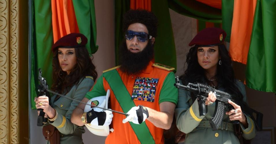 "O ator Sacha Baron Cohen, vestido como o General Aladeen, posa ao lado de duas mulheres com armas para promover o filme ""O Ditador"" (16/5/12)"