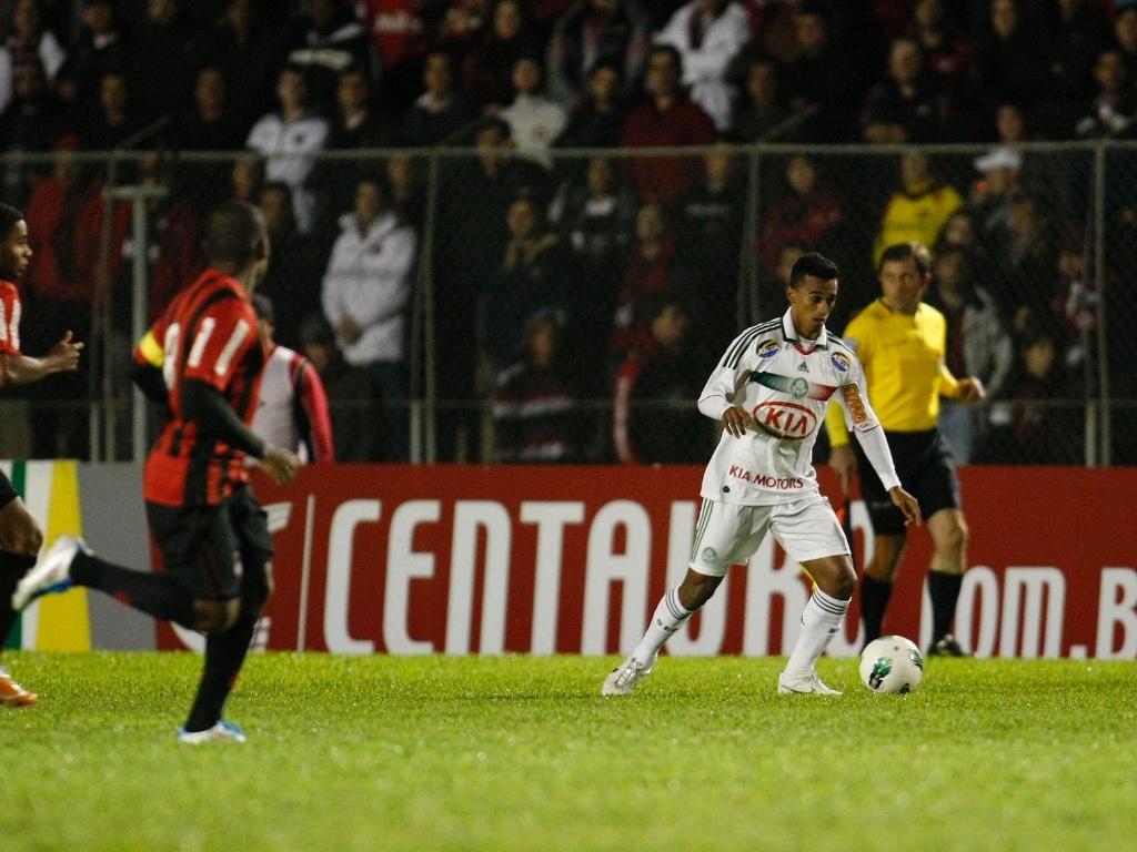 Observado por dois jogadores do Atlético-PR, lateral Juninho, do Palmeiras, conduz a bola no empate por 2 a 2 entre as equipes