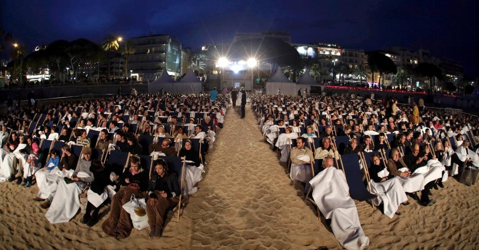 Com cobertores nas pernas, espectadores assistem a exibição de filme na praia em Cannes (17/5/12)