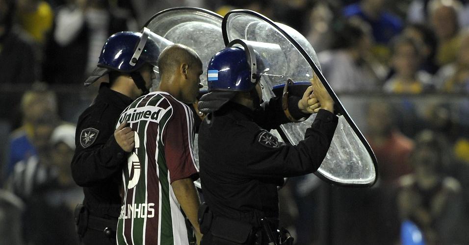 Protegido por policiais, Carlinhos deixa o campo após ser expulso durante a partida contra o Boca Juniors