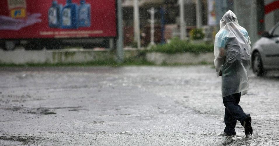 18.mai.2012 - Protegido por uma capa plástica, homem caminha por rua de Salvador, na Bahia, durante chuva que atingiu a capital baiana