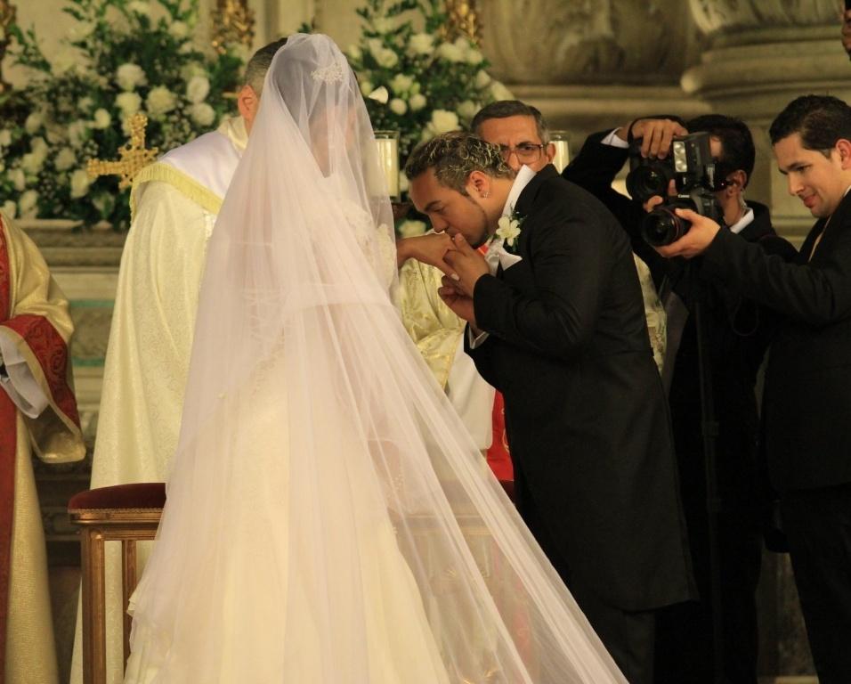 Belo beija a mão da noiva depois da troca de alianças com a noiva Gracyanne Barbosa
