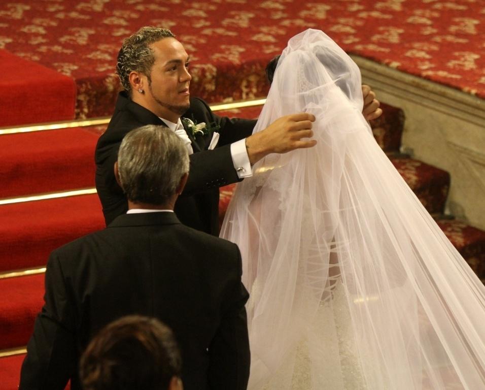 O cantor Belo, no momento em que levanta o véu de Gracyanne Barbosa, o acessório da noiva tem quase três metros de comprimento