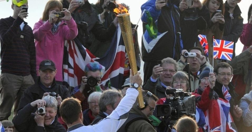 Ao erguer a tocha olímpica, Ben Ainslee anima os torcedores ingleses