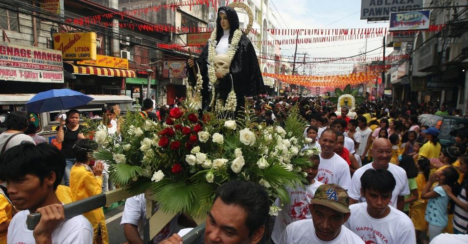 20.mai.2012 - Fiéis levam imagem durante festival religioso em homenagem a Santa Rita de Cássia em Manila, nas Filipinas