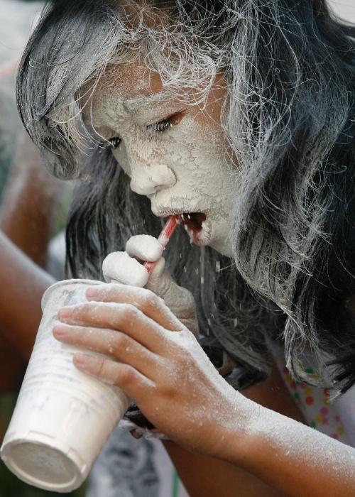 20.mai.2012 - Garota usa canudo para assoprar farinha dentro de um copo de plástico em brincadeira durante festival religioso em homenagem a Santa Rita de Cássia em Manila, nas Filipinas