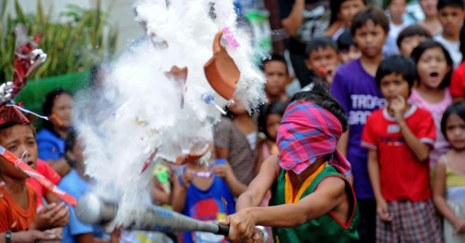 20.mai.2012 - Garoto vendado tenta acertar pote de doces e moedas em brincadeira durante festival religioso em homenagem a Santa Rita de Cássia em Manila, nas Filipinas