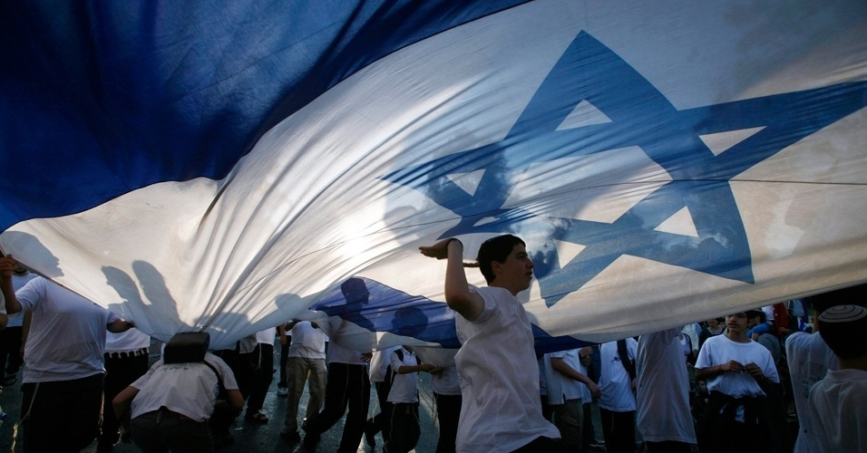 20.mai.2012 - Jovem israelense dan&#231;a embaixo da bandeira nacional durante um desfile em comemora&#231;&#227;o ao Dia de Jerusal&#233;m, neste domingo (20). O feriado marca a liberta&#231;&#227;o da cidade e sua reunifica&#231;&#227;o ap&#243;s a Guerra dos Seis Dias