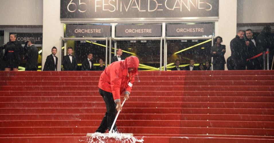 Funcionário retira água do tapete vermelho de Cannes. Uma forte chuva danificou uma das salas do evento e forçou o cancelamento de duas sessões (20/5/12)