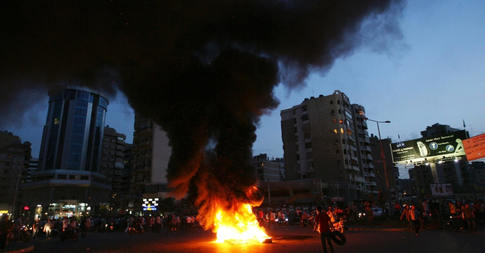 22.mai.2012 - Libaneses mul&#231;umanos xiitas bloqueiam rua em Beirute, no L&#237;bano, com pneus em chamas em protesto contra o sequestro de homens libaneses xiitas no norte da cidade s&#237;ria de Aleppo. Ao menos 13 homens libaneses xiitas, que estavam voltando de peregrina&#231;&#227;o no Ir&#227;, foram sequestrados por rebeldes s&#237;rios