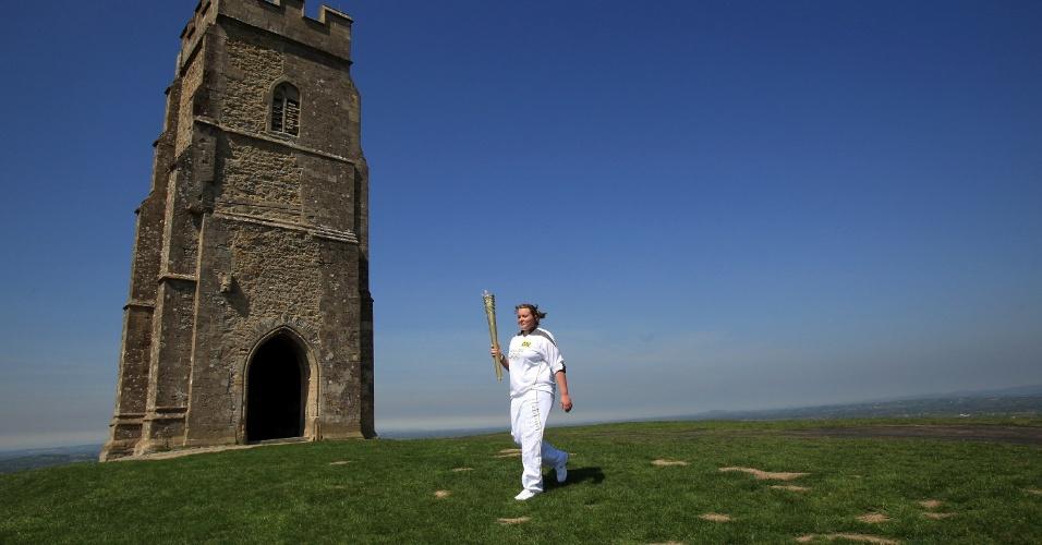Carregadora da tocha olímpica passa por Glastonbury Tor, pequena montanha localizada na cidade de Glastonbury, sul da Inglaterra