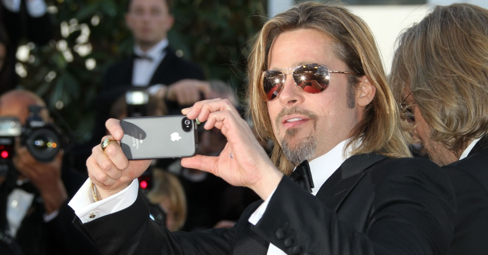 "O ator Brad Pitt, que está no elenco de ""Killing them Softly"", tira fotos do público ao chegar à exibição do filme no Festival de Cannes 2012 (22/5/12)"