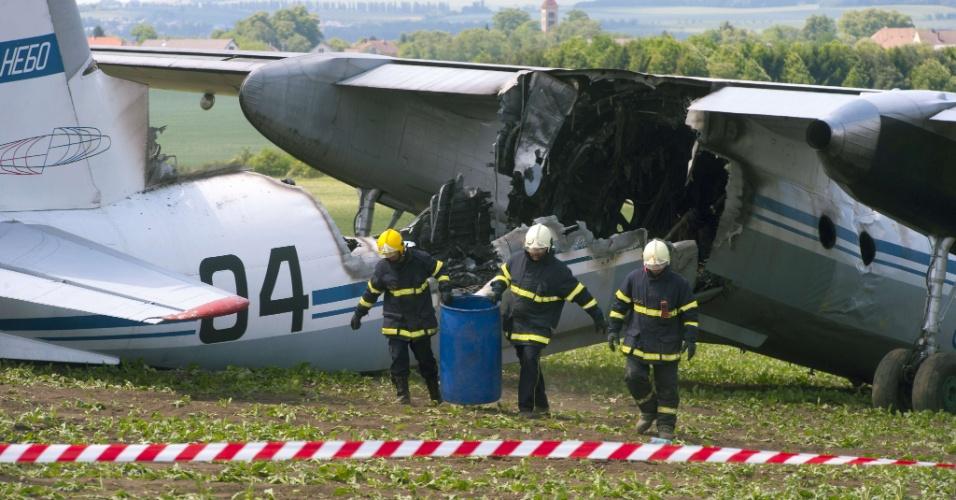 23.mai.2012 - Bombeiros retiram destroços de um avião militar russo Antonov An-30 que derrapou em um campo momentos antes de aterrissar na base aérea de Caslav, a 80 km de Praga, na República Tcheca. Sete pessoas ficaram feridas -- duas delas com queimaduras graves, após a aeronave pegar fogo