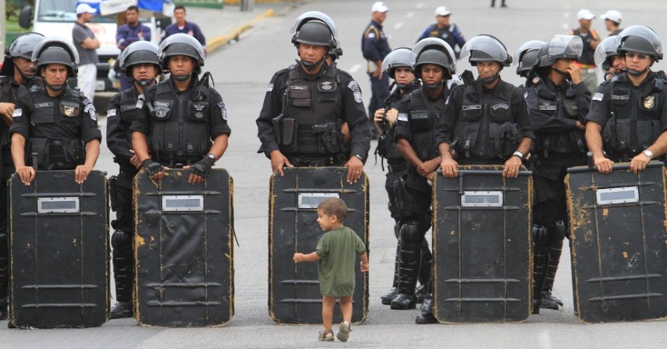 23.mai.2012 - Criança brinca em frente a corrente de policiais durante operação de retirada de cerca de 40 famílias que moravam nas comunidades do Bom Jesus e Bariloche, localizadas nas proximidades do túnel Augusto Lucena, em Boa Viagem, zona sul do Recife (PE)
