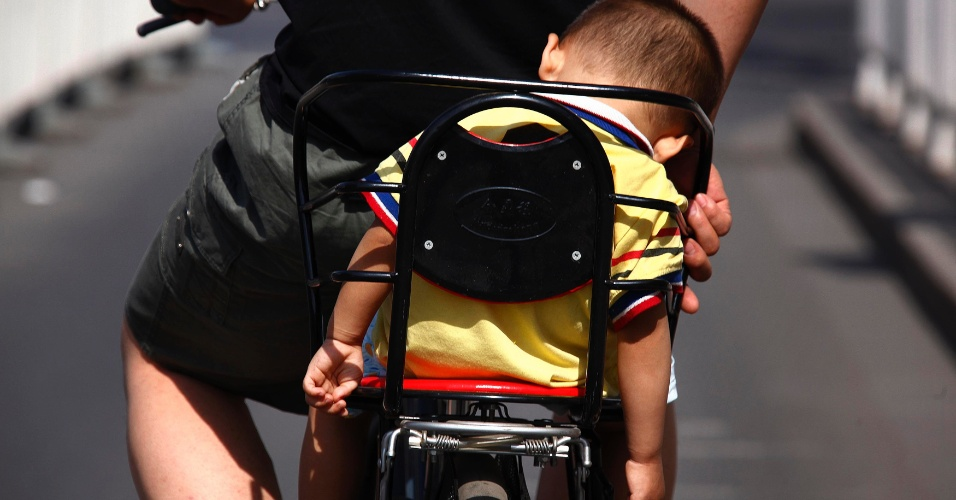 23.mai.2012 - Garoto dorme no banco de trás de uma bicicleta nesta quarta (23) em Pequim, na China
