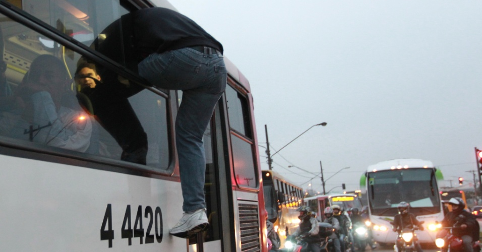 23.mai.2012 - Usu&#225;rio entra em &#244;nibus p&#250;blico pela janela, ap&#243;s protesto na Radial Leste, ao lado da esta&#231;&#227;o Corinthians-Itaquera, da linha 3-vermelha do Metr&#244; de S&#227;o Paulo, na manh&#227; desta quarta-feira (23)