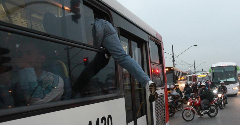 23.mai.2012 - Usuário entra em ônibus público pela janela, após protesto na Radial Leste, ao lado da estação Corinthians-Itaquera, da linha 3-vermelha do Metrô de São Paulo, na manhã desta quarta-feira (23)