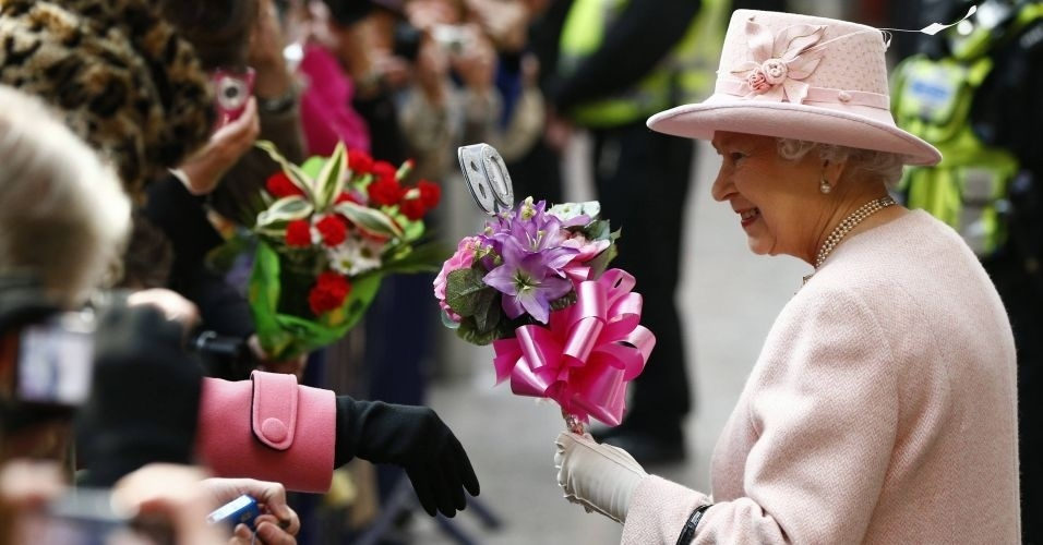 23.mar.2012 - Rainha Elizabeth recebe flores ao desembarcar na esta&#231;&#227;o Victoria em Manchester, norte da Inglaterra. A viagem integra o tour pela Gr&#227;-Bretanha em comemora&#231;&#227;o ao seu Jubileu de Diamante