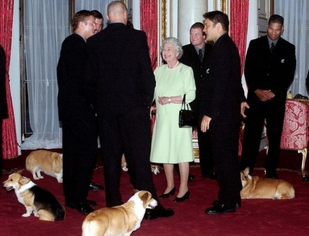 5.nov.2002 - Rainha Elizabeth 2ª e sua comitiva de cães Corgi encontram o time de rubgy New Zealand All Blacks, da Nova Zelândia, no Palácio de Buckingham