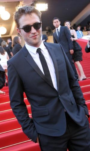 """O ator Robert Pattinson posa para fotos no tapete vermelho ao chegar à exibição de """"Na Estrada"""", que tem sua namorada Kristen Stewart no elenco, no Festival de Cannes 2012 (23/5/12)"""