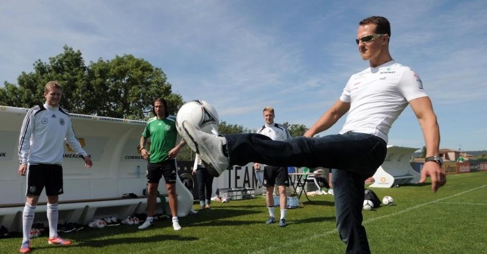 O piloto Michael Schumacher bate bola com os jogadores da seleção alemã
