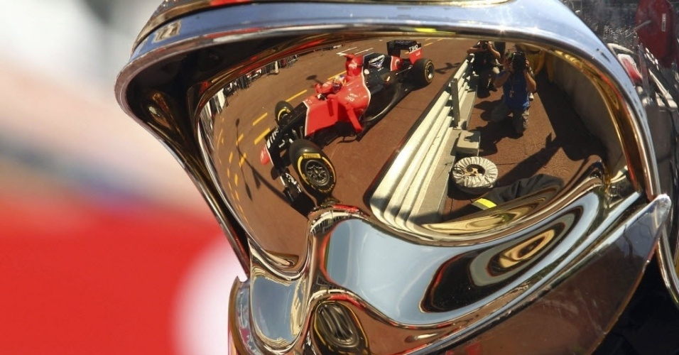 Carro do piloto Timo Glock, da Marussia, é refletido no óculos do mecânico da escuderia