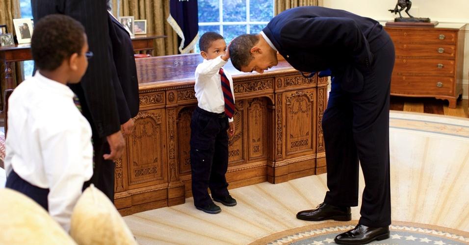Em foto sem data, Jacob Philadelphia, 5, filho de um funcionário da Casa Branca, toca o cabelo do presidente Barack Obama no Salão Oval, em Washington