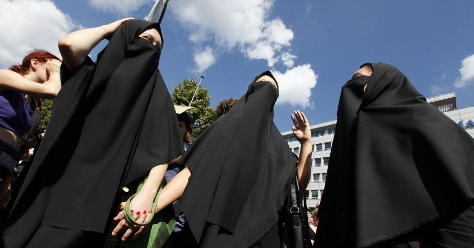 13.ago.2011 - Em protesto contra o abuso sexual de mulheres, manifestantes usam burca durante comício do SlutWalk, em Berlim (Alemanha). A intenção é criticar o costume de culpar a vítima pelo estupro