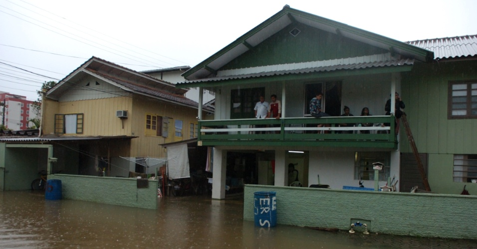 25.mai.2012 - A cidade de Blumenau (SC) registrou alagamentos e deslizamentos de terra por conta de chuvas. Na foto, moradores passaram a noite tentando salvar móveis no bairro da Velha