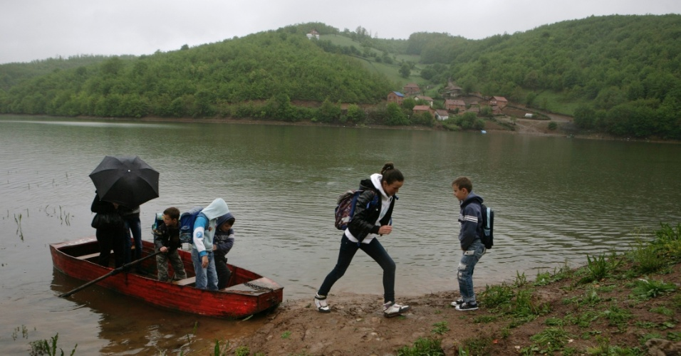 25.mai.2012 - Alunos atravessam o lago Batllava em barco para ir &#224; escola no vilarejo de Orllane, no Kosovo. O lago artificial abastece a cidade de Pristina