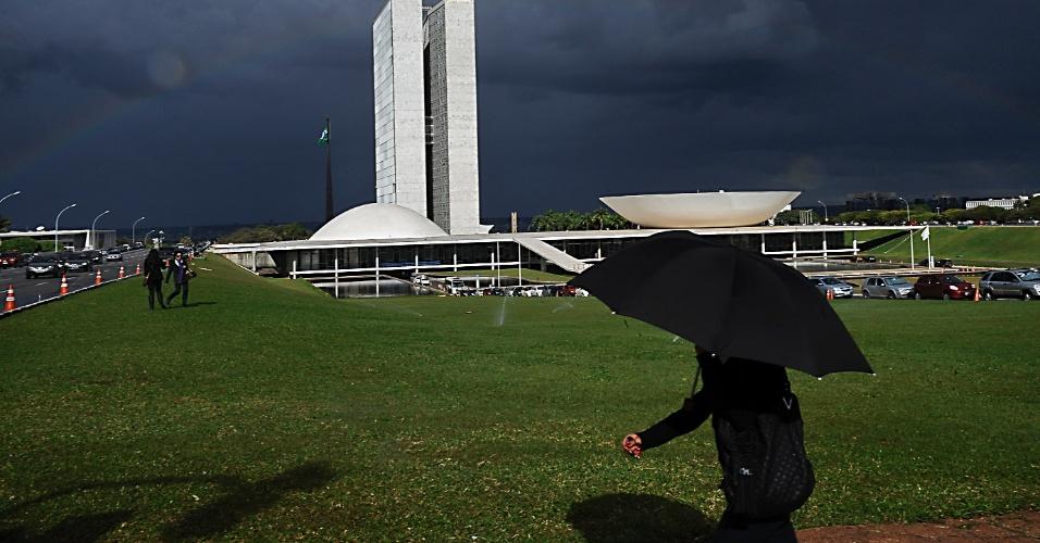 25.mai.2012 - Brasiliense usa guarda-chuva para se proteger da chuva que atingiu Brasília na tarde desta sexta-feira. Apesar da proximidade do inverso, a tempestade foi típica dos meses de verão