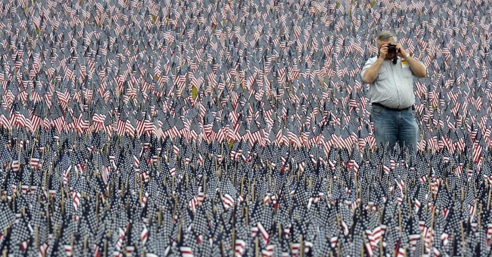 25.mai.2012 - Homem tira fotos em instalação com 33 mil bandeiras americanas em homenagem a soldados mortos, durante o ?Memorial Day? realizado em Boston, nos EUA