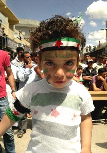25.mai.2012 - Menino participa de protesto contra o ditador sírio, Bashar al Assad, em Maraa, perto de Aleppo, no norte da Síria. O ato ocorreu após as tradicionais orações das sextas-feiras