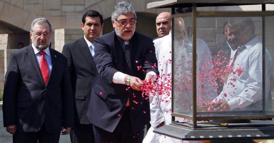 25.mai.2012 - O presidente do Paraguai, Fernando Lugo, joga pétalas de rosa sobre o Memorial Mahatma Gandhi, em Nova Dél, na Índia