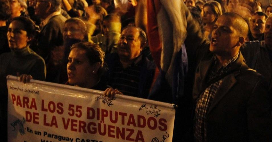 """25.mai.2012 - Paraguaios protestam em frente ao Congresso Nacional, em Assunção, contra o aumento do orçamento aprovado para assistentes políticos. O banner na frente diz: """"Para os 55 deputados da vergonha"""""""