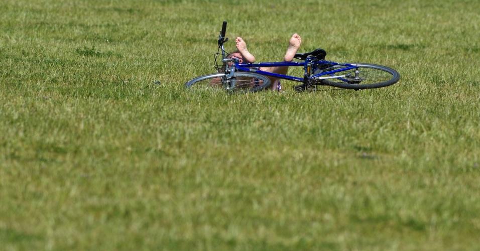 25.mai.2012 - Rapaz aproveita o sol deitado na grama em Berlim, na Alemanha, nesta sexta-feira (25). Meteorologistas apontam tempo quente com temperaturas rondando 25º C na próxima semana no país